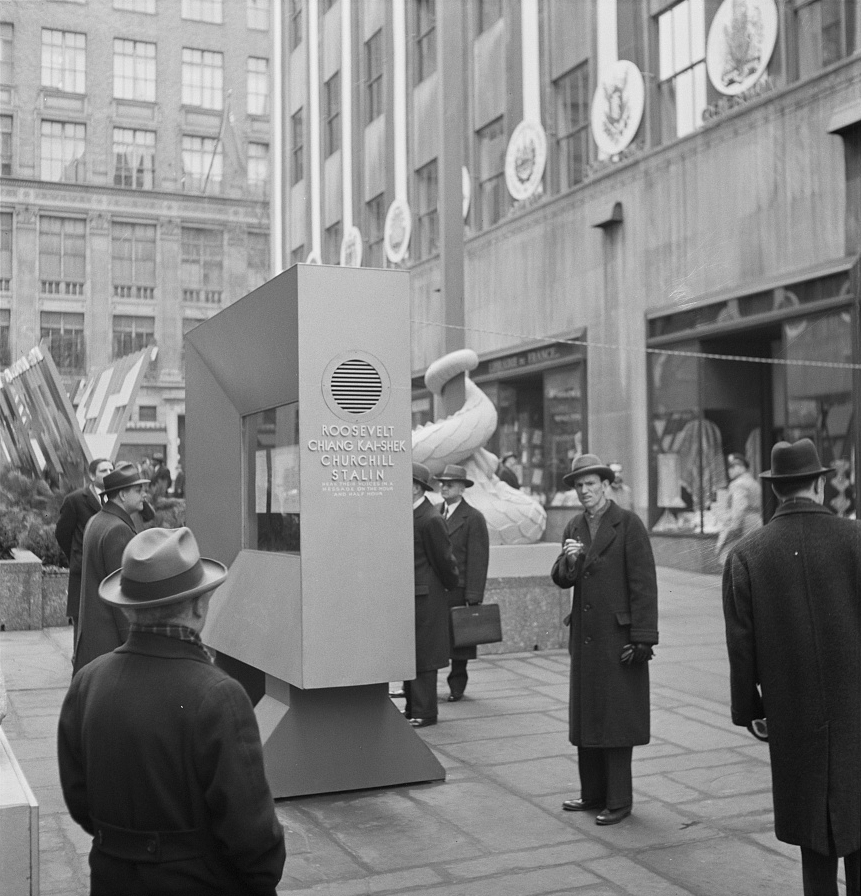 "New York, New York. ""United Nations"" exhibition of photographs presented by the United States Office of War Information (OWI) on Rockefeller Plaza. Listening to broadcasts of President Roosevelt, Churchill, Stalin, and Chiang Kai-shek, heard every half-hour from a loudspeaker at one end of the frame containing the Atlantic charter. This frame is surrounded by four statues of the four freedoms"